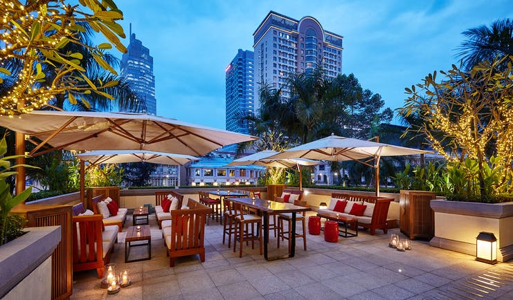 Park Hyatt Saigon terrace, outdoor dining area, tables and chairs covered with umbrellas, city views