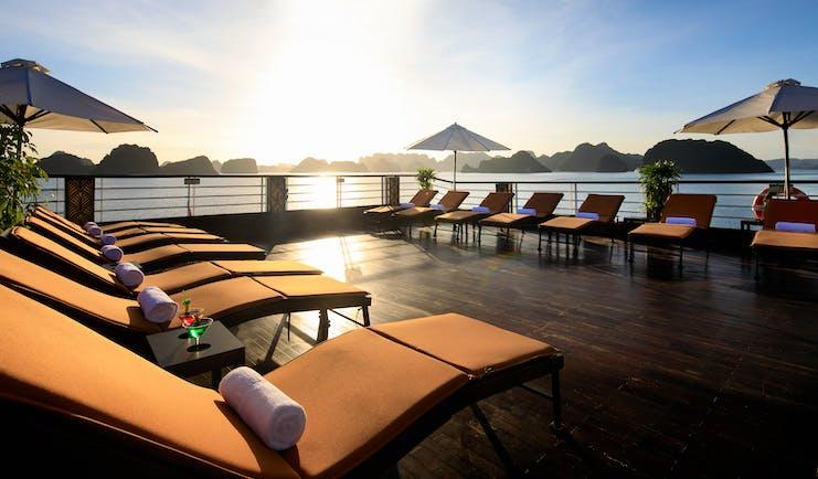 Perla Dawn Sails Cruise sundeck, sun loungers, umbrellas, views over the bay