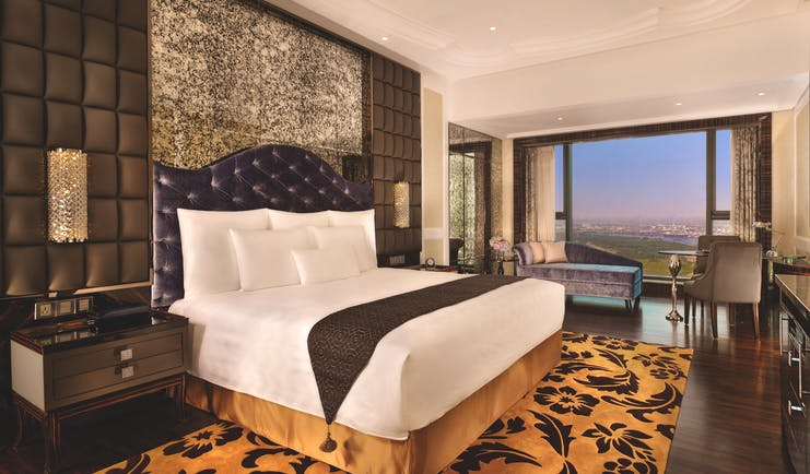 View of a deluxe room at the Reverie Saigon with a large bed, leopard print rug, television and big windows with a view over vietnam