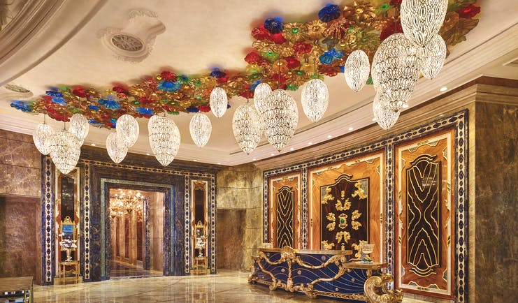 Main lobby at the Reverie Saigon with multiple large chandeliers hanging from the ceiling, gold panelling in the waters and marble floors