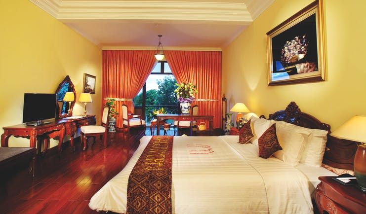 Colonial suite at the Saigon Morin Hotel with large bed, a television, paintings with gold frames and a yellow and red colour scheme