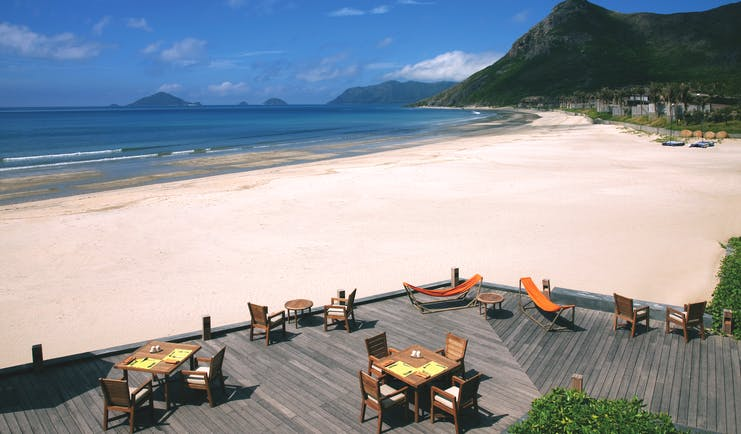 Six Senses Vietnam beach deck terraced seating area on beach front mountains in background