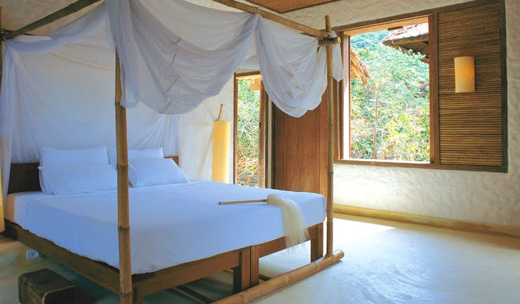 Six Senses Ninh Van Bay Vietnam bedroom white four poster bed with drapes garden view
