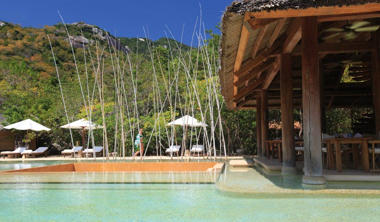 Six Senses Ninh Van Bay Vietnam outdoor pool loungers umbrellas covered seating area