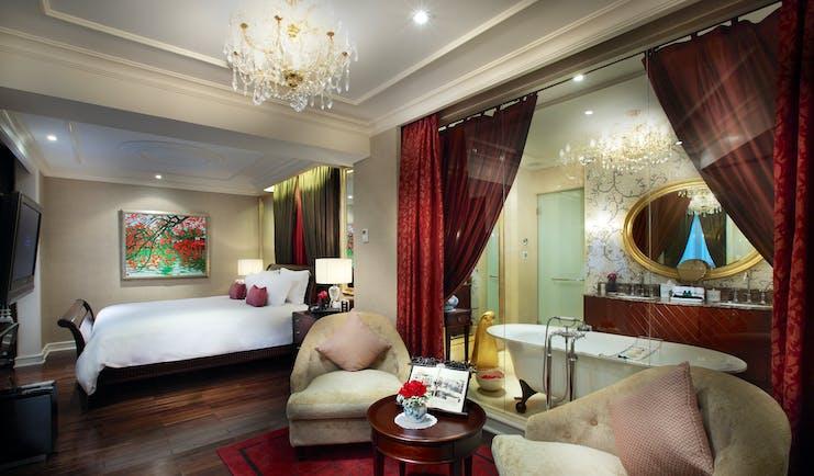 Sofitel Metropole Hanoi grand prestige suite, bed, armchairs, en suite bathroom behind glass wall