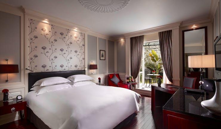 Sofitel Metropole Hanoi premium room, double bed, armchair, doors leading to garden, elegant decor