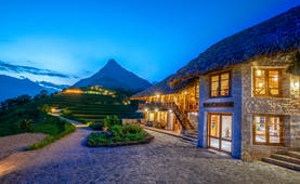 Topas Ecolodge exterior, thatched building, path, mountain in background