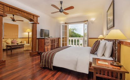 Victoria Can Tho Resort colonial suite, double bed, living area with sofa, modern decor, balcony