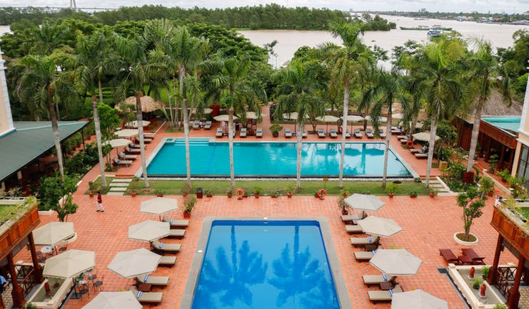 Victoria Can Tho Resort pools, sun loungers, palm trees, bay in background