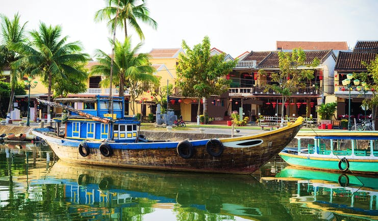 Wooden boat moored up Thu Bon River in Hoi An, riverside houses, palm trees