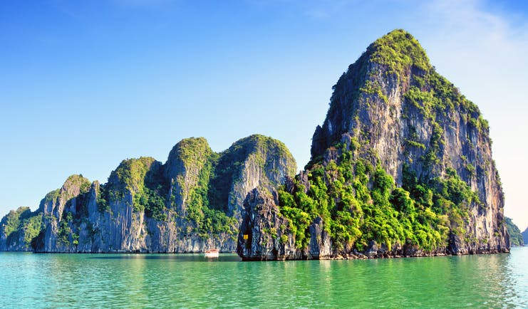 Ha Long Bay rock formation in sea, tall rocks covered in greenery