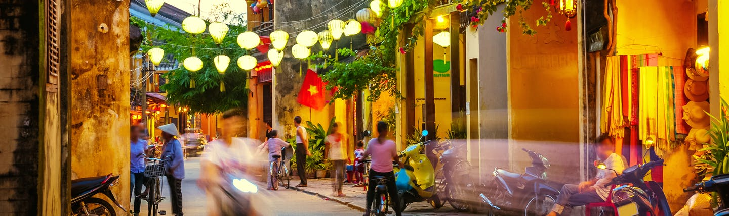 Hoi An street, lanterns, motorbikes, people chatting, buildings, plants