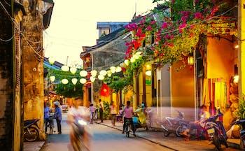 Hoi An street, lanterns, motorbikes, people chatting, buildings, plants