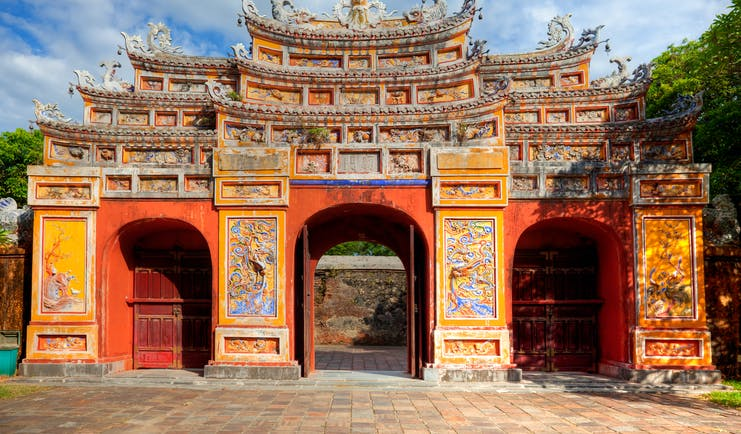 Gate at the imperial city citadel in Hue, colourful structure with carvings and paintings