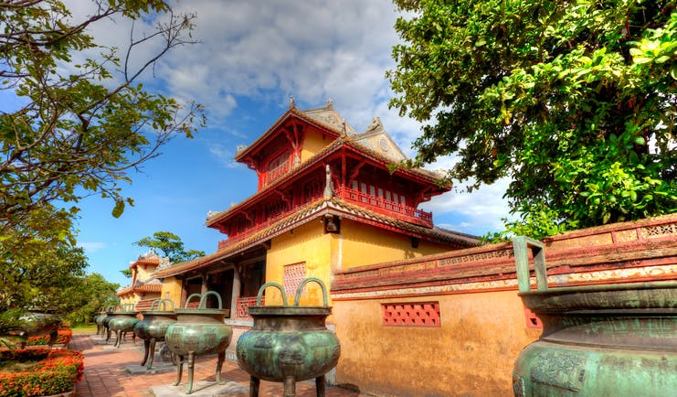 Part of the Imperial Palace in Vietnam, exterior, traditional architecture, red details, yellow walls, large stone vases
