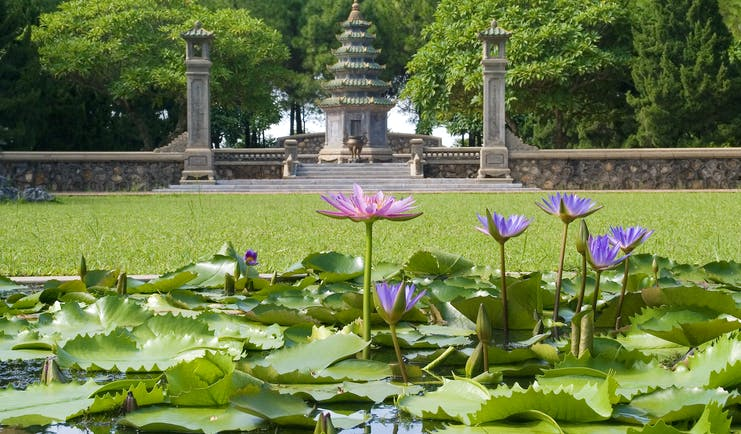 Thien Mu Pagosa, pink and purple water lilies, verdant lawn, intricate pagoda