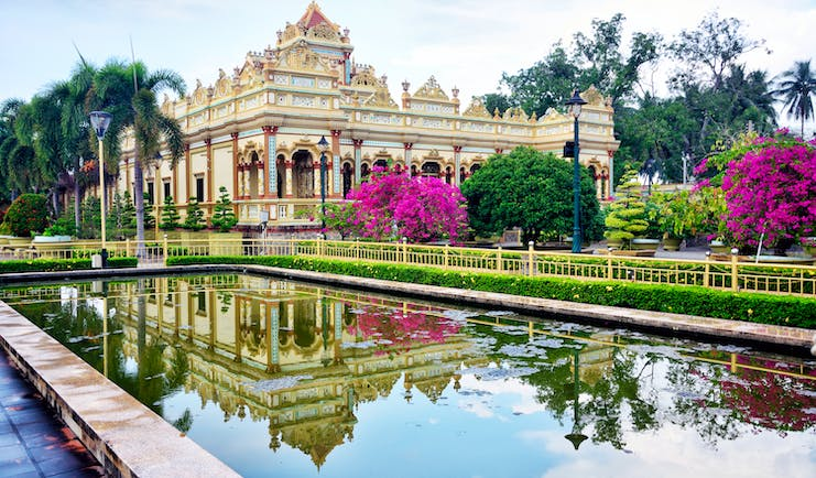Vinh Trang Temple, pond, trees, pink flowers, intricate architecture, columns, temple facade
