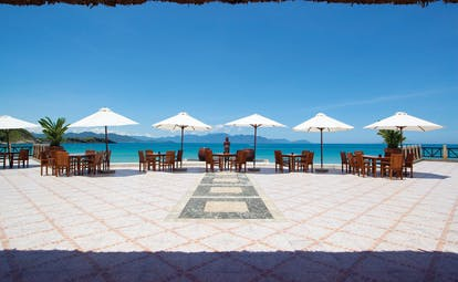 Vinpearl Luxury Nha Trang Vietnam beach view dining terrace tables chairs umbrellas