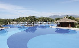 Vinpearl Luxury Nha Trang Vietnam pool palm trees mountains in background