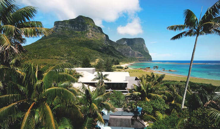 Capella Lodge exterior, modern architexture, exterior seating area, lush greenery, beach and mountains in background