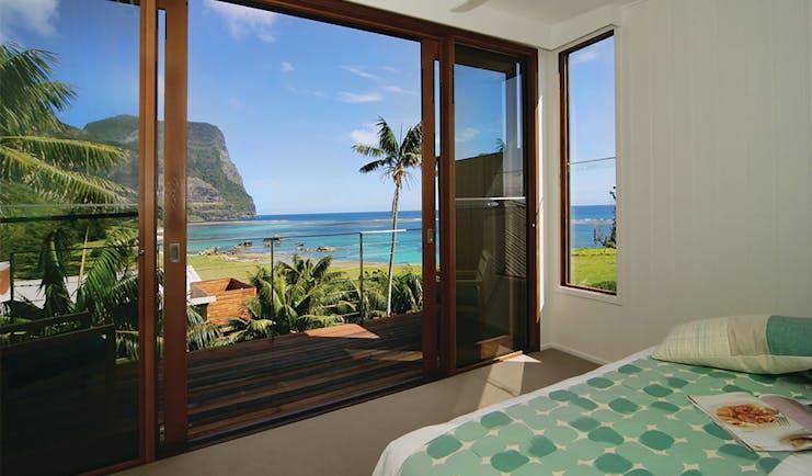 Capella Lodge lagoon loft guestroom, double bed, balcony overlooking bay and coastline