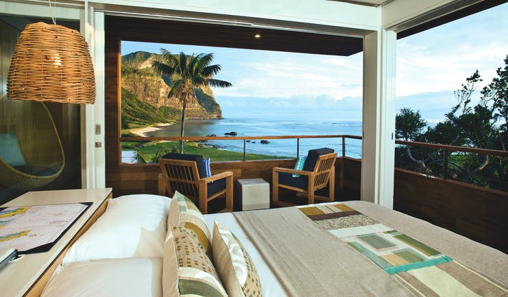 Capella Lodge Lidgbird Pavilion guestroom, double bed, chairs, room overlooking bay and coastlibe