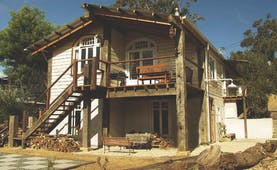 Old Leura Dairy New South Wales exterior wooden building with log piles and stairs up to rooms