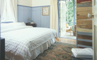 Old Leura Dairy New South Wales workers bedroom with blue and white wooden walls and patio door to balcony