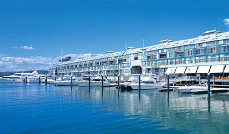 Ovolo Woolloomooloo Sydney exterior waterfront building with awnings near marina with boats