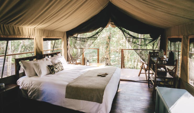 Paperbark Camp New South Wales safari interior tent with large white bed and view of trees