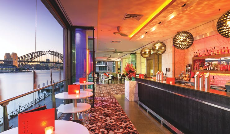 Pullman Grand Quay Sydney bar area with view of harbour bridge at night
