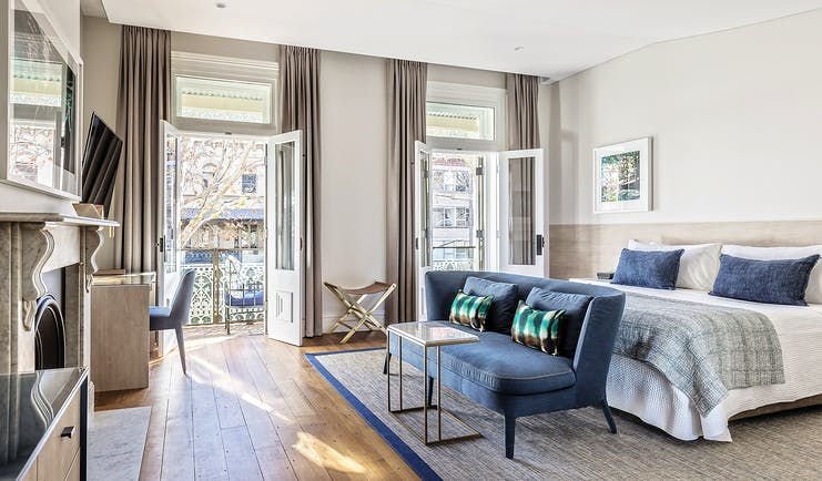 Spicers Potts Point view from a terrace suite with large double bed, and windows opening onto a balcony