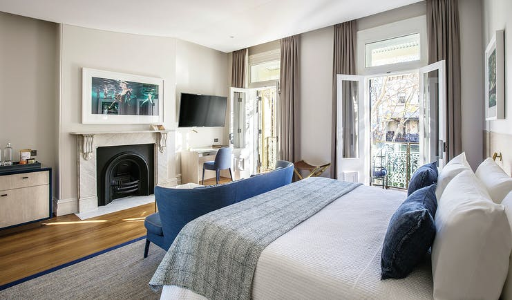 Spicers Potts Point terrace suite with double bed, open fireplace, and balcony