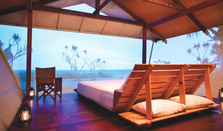 Bamurru Plains lodge interior, double futon bed, netted walls overlooking outback