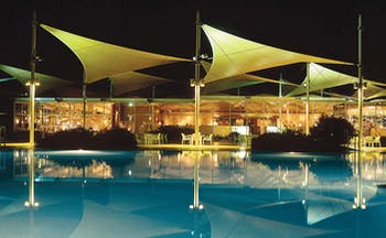 Sails in the Desert Ayers Rock outdoor pool overlooked by glass building with metal sail sculptures