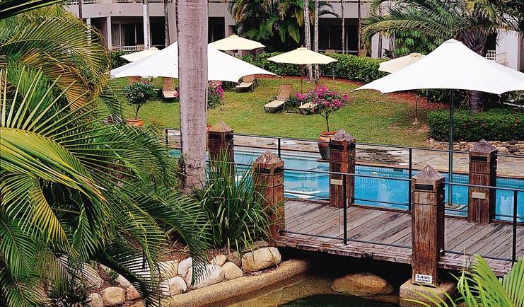 Alamanda Palm Cove Queensland outdoor pool with  wooden bridge loungers and umbrellas