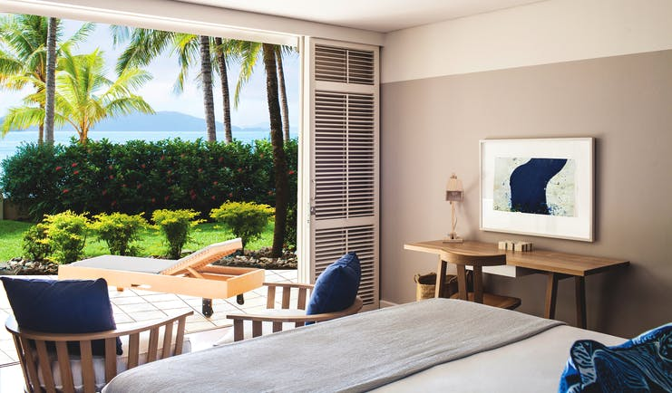 Beach Club Hamilton guestroom, double bed, modern decor, doors leading to terrace with sun loungers, overlooking the sea
