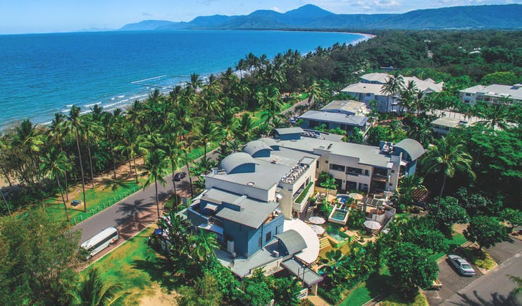 Port Douglas Peninsula Queensland aerial beach view of hotel complex with outdoor pool and palm trees near coast