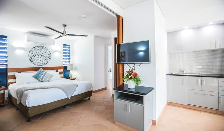Port Douglas Peninsula Queensland suite with white kitchen and bedroom and television