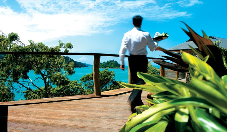 Qualia Hamilton Island Queensland boardwalk waiter with tray walking along a boardwalk