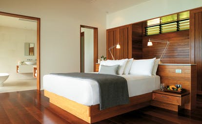 Qualia Hamilton Island Queensland Windward bedroom with wooden walls and floors and view of bathroom