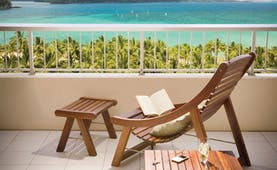 Reef View balcony, wooden deck chair and footstall overlooking turquoise blue sea