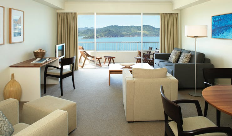 Reef View suite lounge, armchairs, desk, sofa, modern decor, balcony overlooking the sea