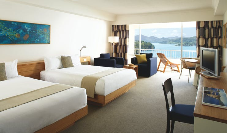 Reef View Twin guestroom, beds, armchairs, bright modern decor, balcony overlooking the sea