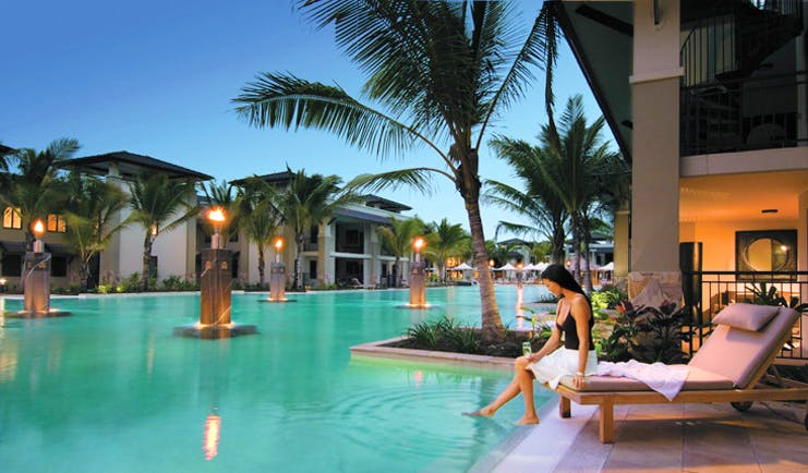 Sea Temple Queensland swimming pool woman sitting on sun lounger palm trees