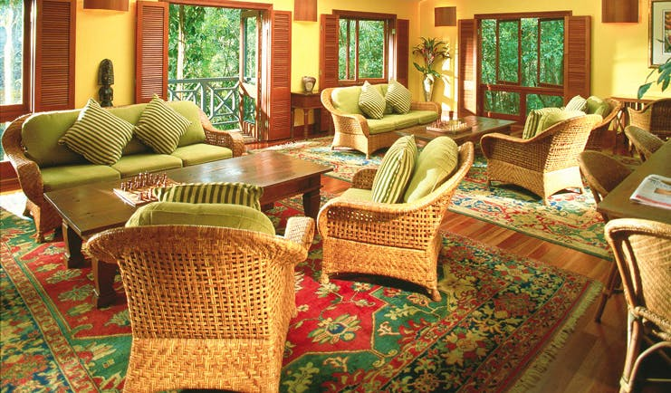 Silky Oaks Lodge Queensland lounge with wicker chairs and sofas and access to balcony