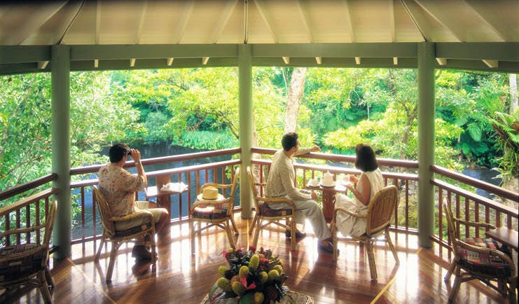 Silky Oaks Lodge Queensland terrace people sitting on a covered terrace overlooking water and trees