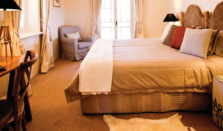 Bedroom with electric overhead fan, large double bed and draping curtains