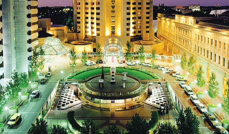 Intercontinental Adelaide view onto hotel at night with a brightly lit plaza below with reen trees lining the walkways