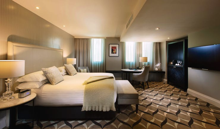 Deluxe king room with large double bed, television and chairs